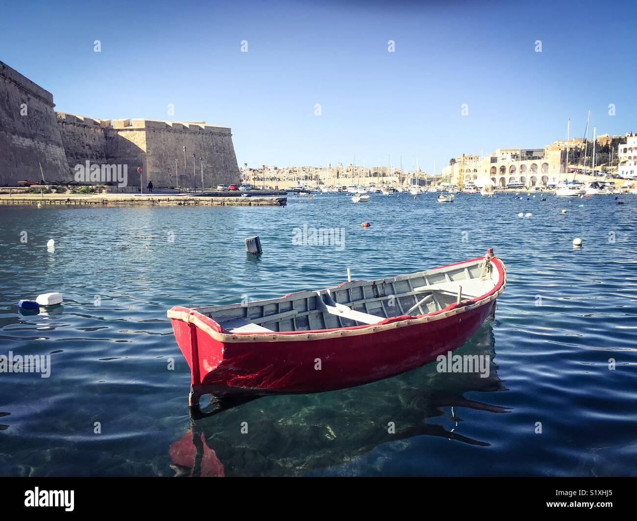 Kleine rote Holz Fischerboot in der Bucht, Kalkara, Malta Stockbild