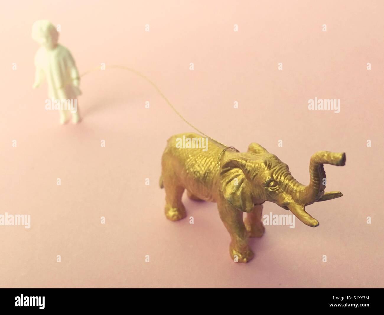 Ein Vintage Doll Figur mit einem goldenen Leine an einem gold elephant Figurine. Stockbild