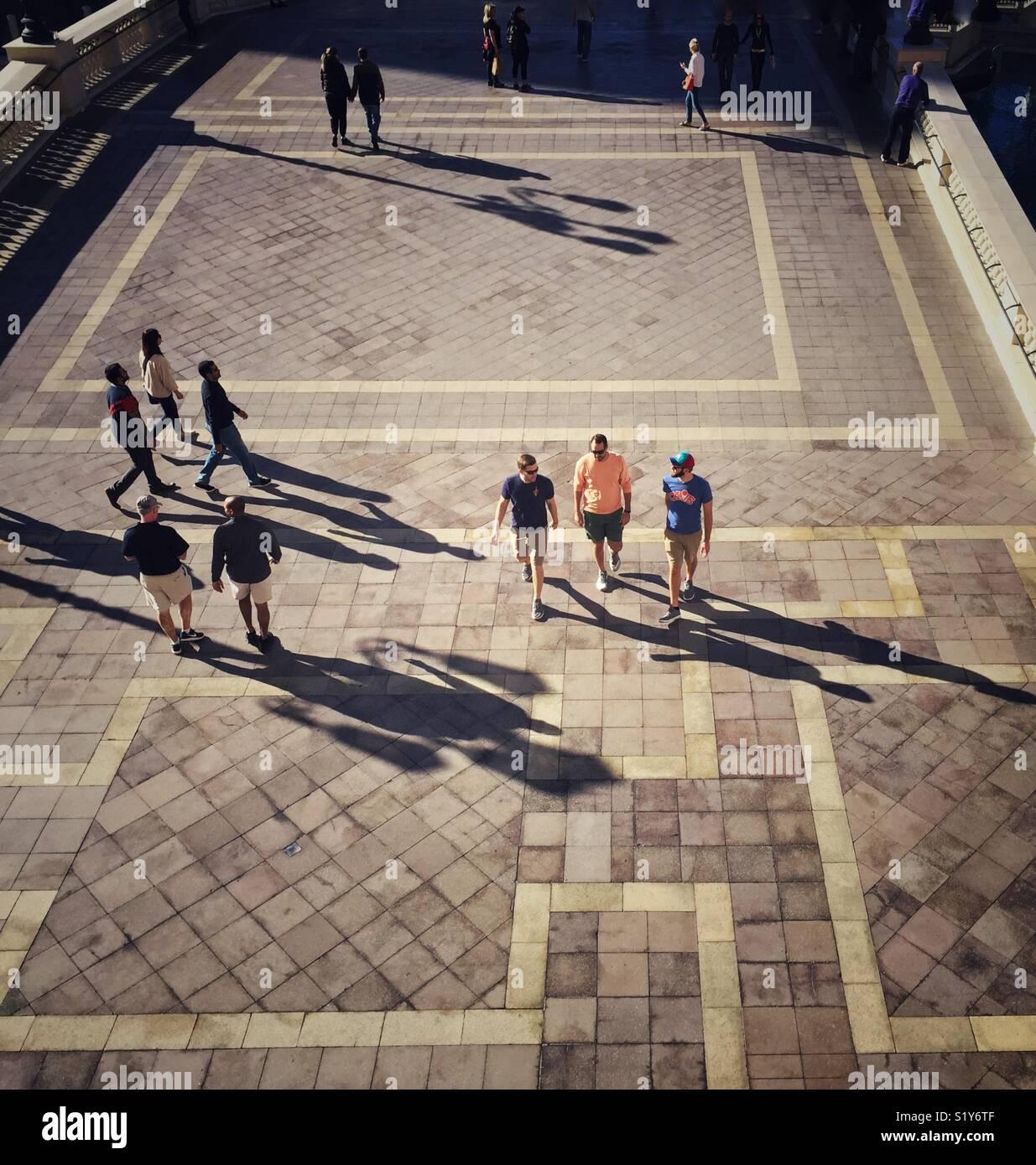 Touristen die Brücke überqueren und werfen lange Schatten auf dem Weg zum Hotel Venetian in Las Vegas, Stockbild
