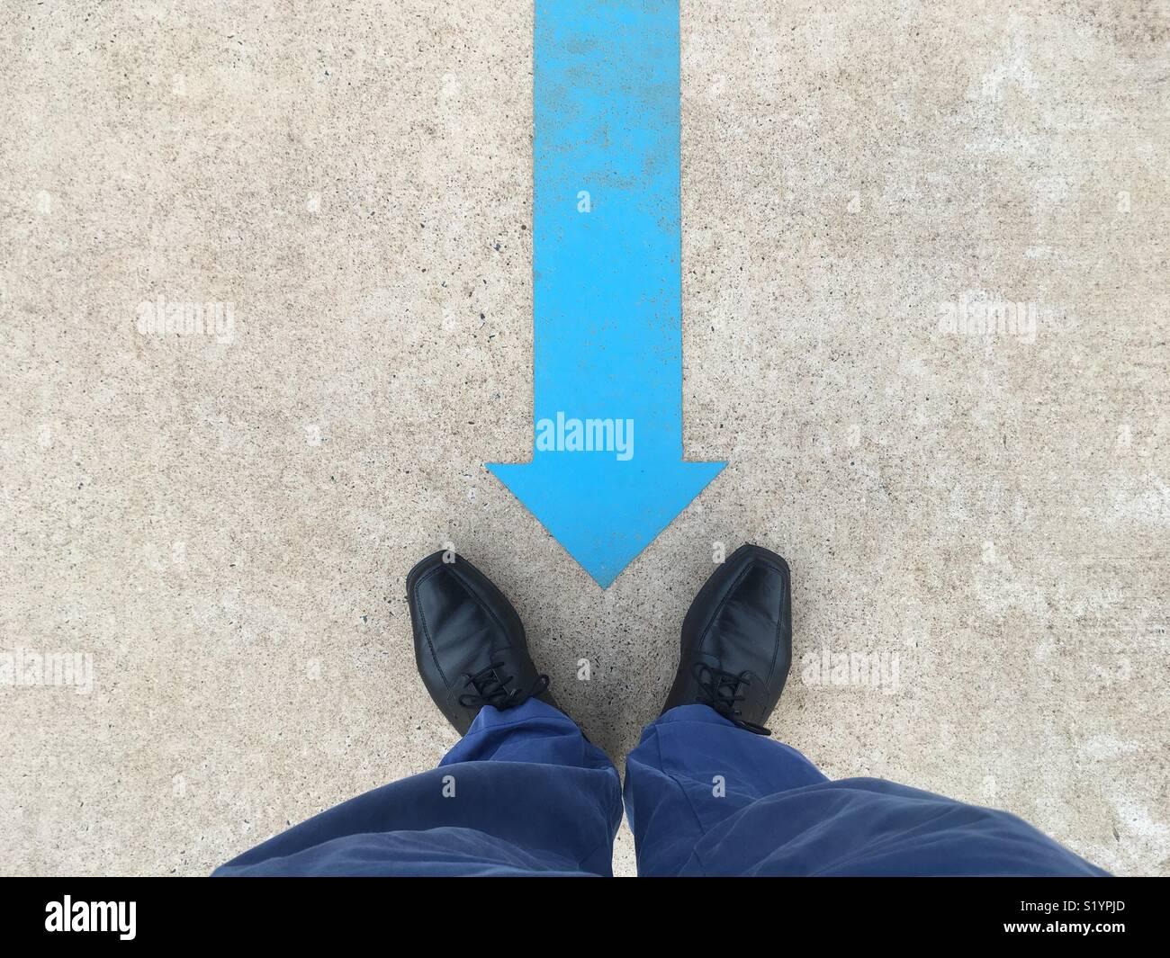 Ein blauer Pfeil auf dem Boden zeigend auf schwarze Schuhe eines Mannes und blauen Hosen gemalt. Stockbild