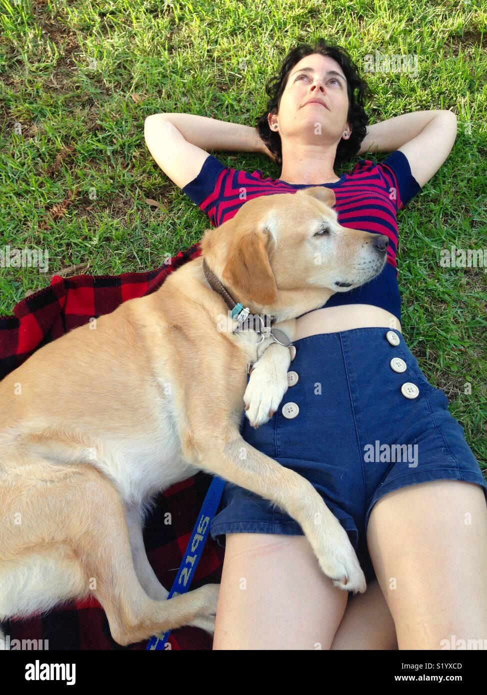 Frau und ihrem Labrador Retriever auf ihr lag auf einer Picknick-Decke in einem Park Stockbild