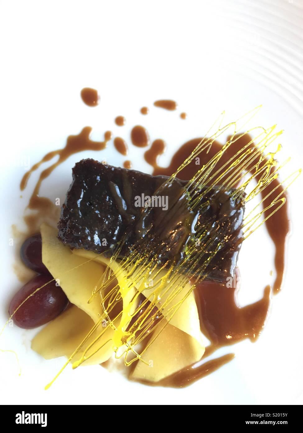 Schön Dessert der Sticky Toffee Pudding mit Spin Zucker Dekoration und Obst vorgestellt Stockbild