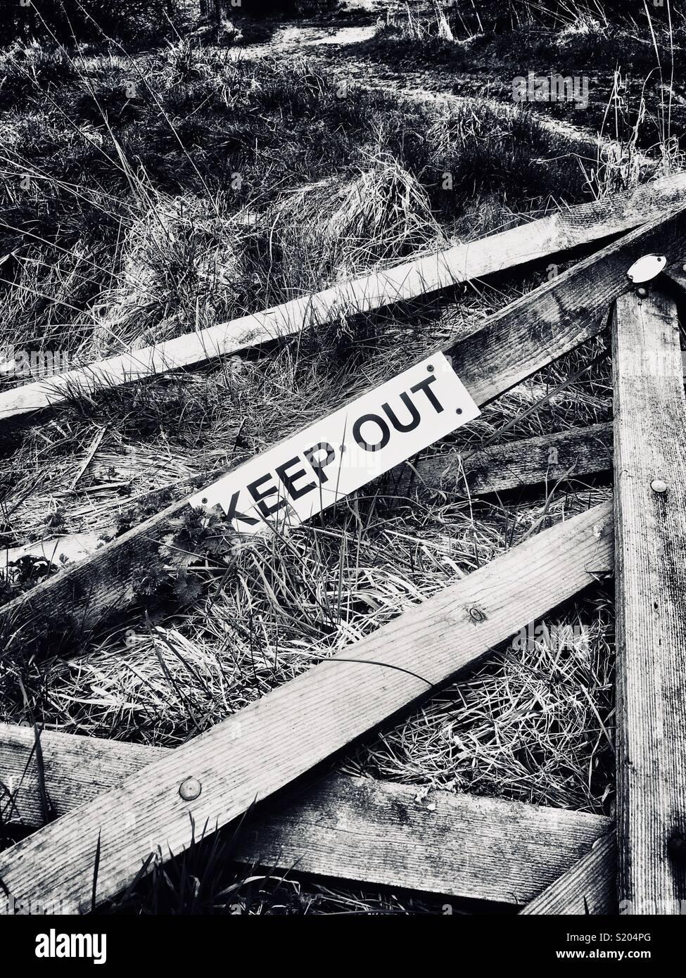 Gebrochene Holz- tor auf Ackerland mit einem halten sich abmelden befestigt Stockbild