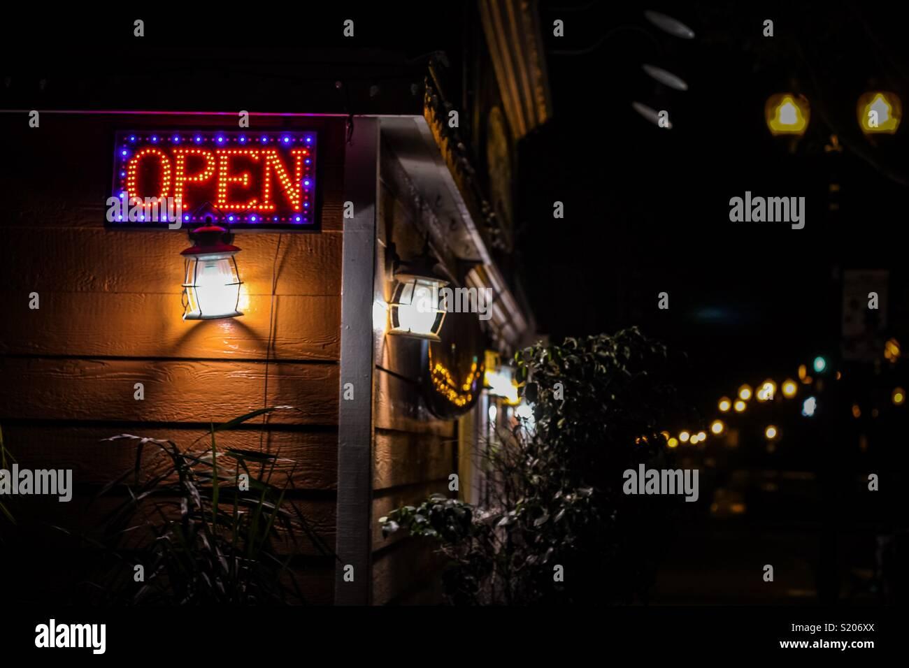 Öffnen Sie die Seite in der Nacht in einer kleinen Stadt mit einem alten Einrichtung leuchtet Stockbild