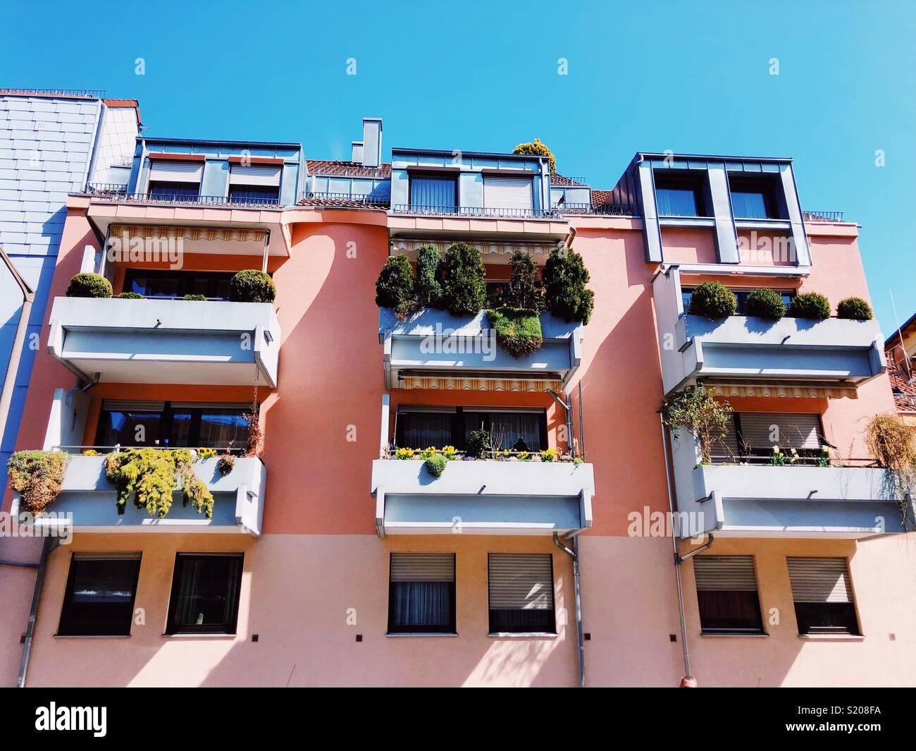 Frühling in der Stadt. Farbige Häuser mit Töpfen Grün auf dem Balkon Stockbild