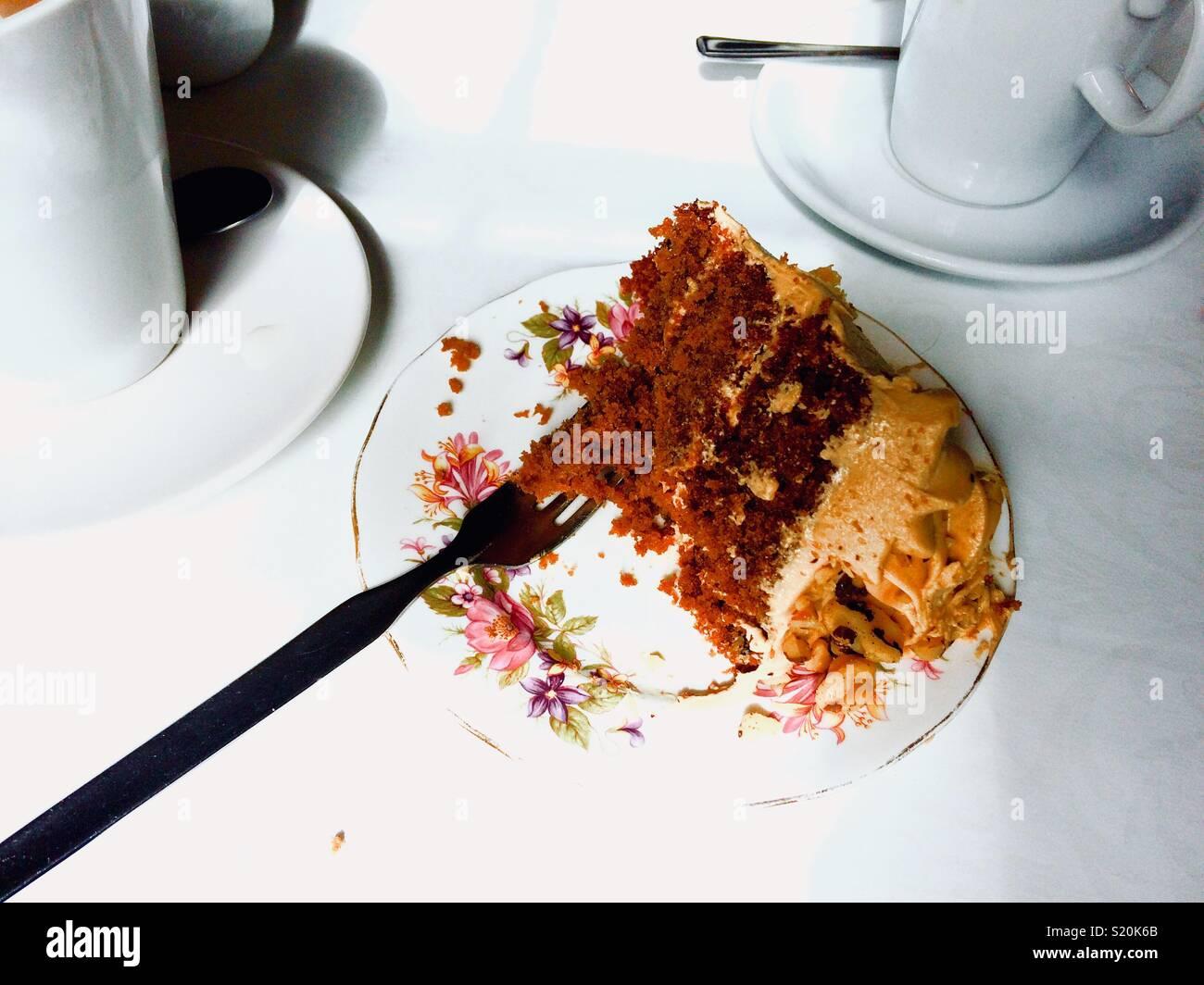 Zufriedenheit: teilweise Kaffee Kuchen auf einem Teller gegessen Stockbild