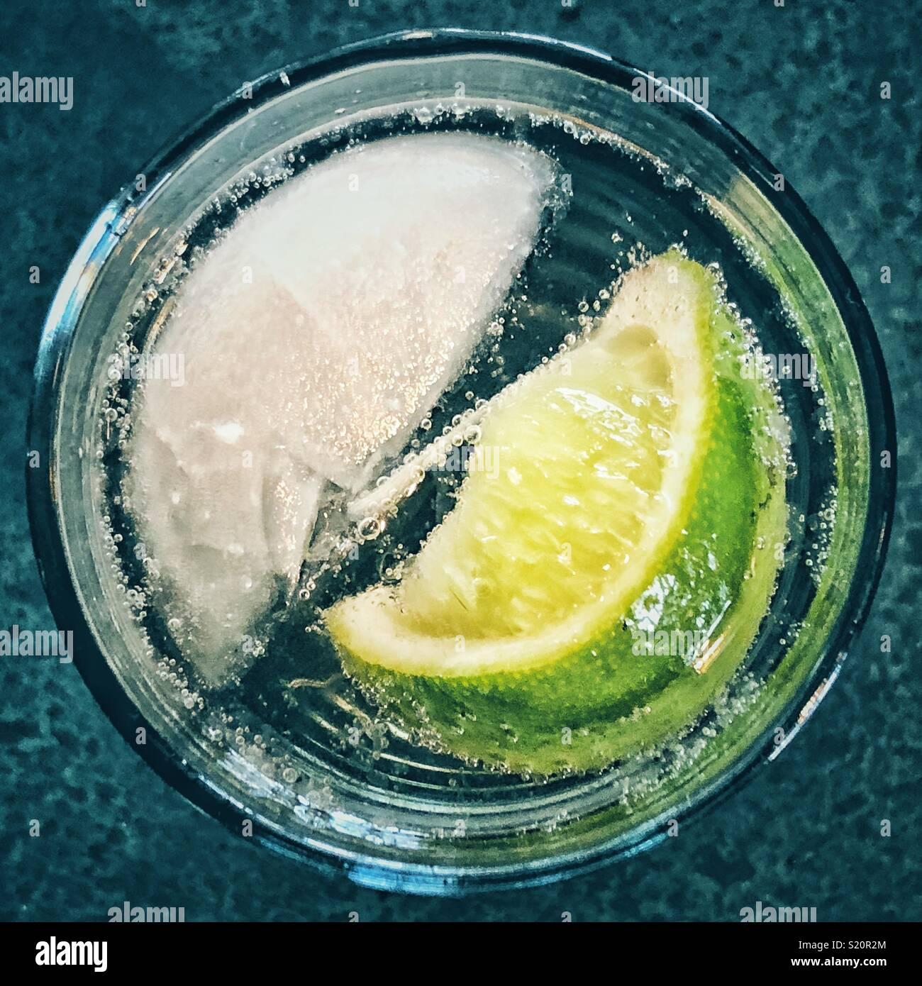 Blick von oben auf die single Ice Cube und Kalk Keil in ein Glas Wasser mit Kohlensäure Stockfoto