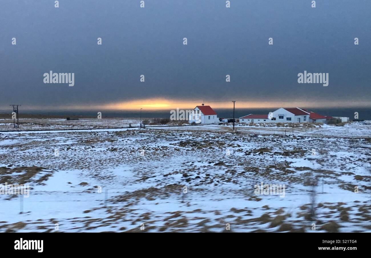 Einsames Haus mit Schnee bedeckten Felder bei Sonnenuntergang Stockbild