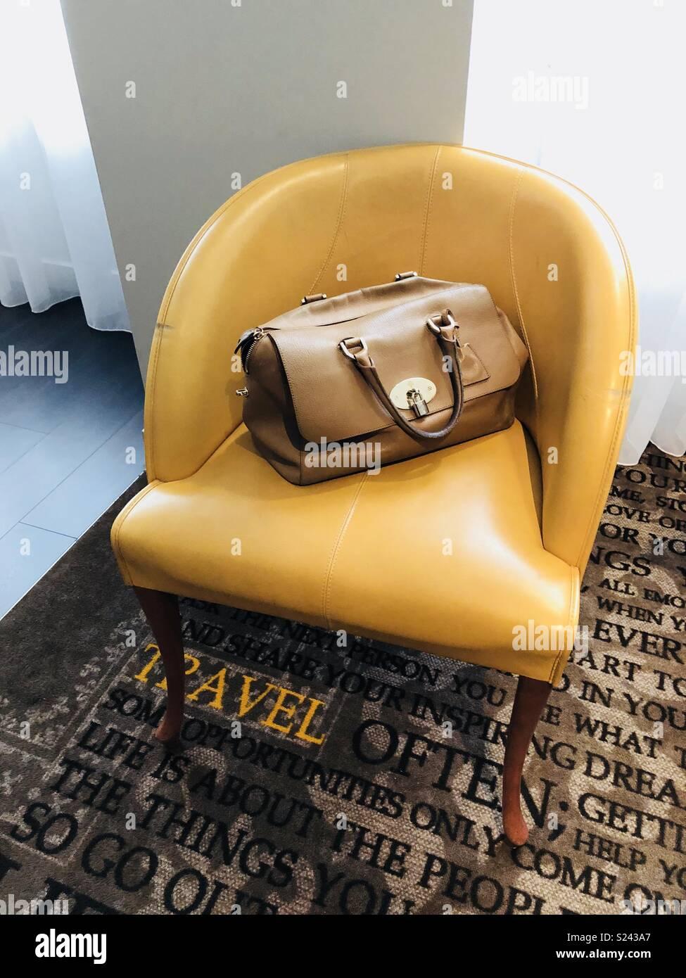 Braun Mulberry Frauen Handtasche Auf Einem Gelben Stuhl Stockfoto