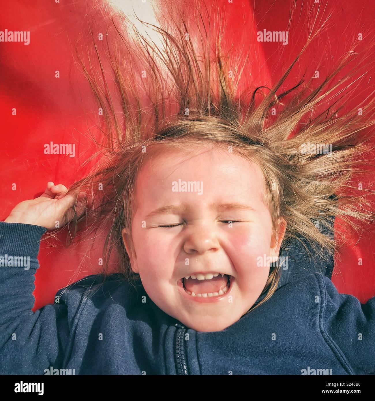 Portrait von Happy toddler girl Gesicht, während sie rutscht eine rote Folie mit geschlossenen Augen, den Mund offen und Haar kleben von statischer Elektrizität Stockbild