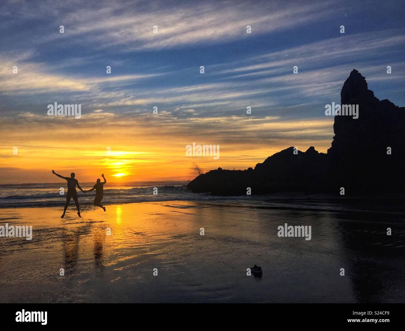 Paar springen halten sich an den Händen, als die Sonne im Hintergrund auf Piha Beach, Auckland, Neuseeland Stockfoto
