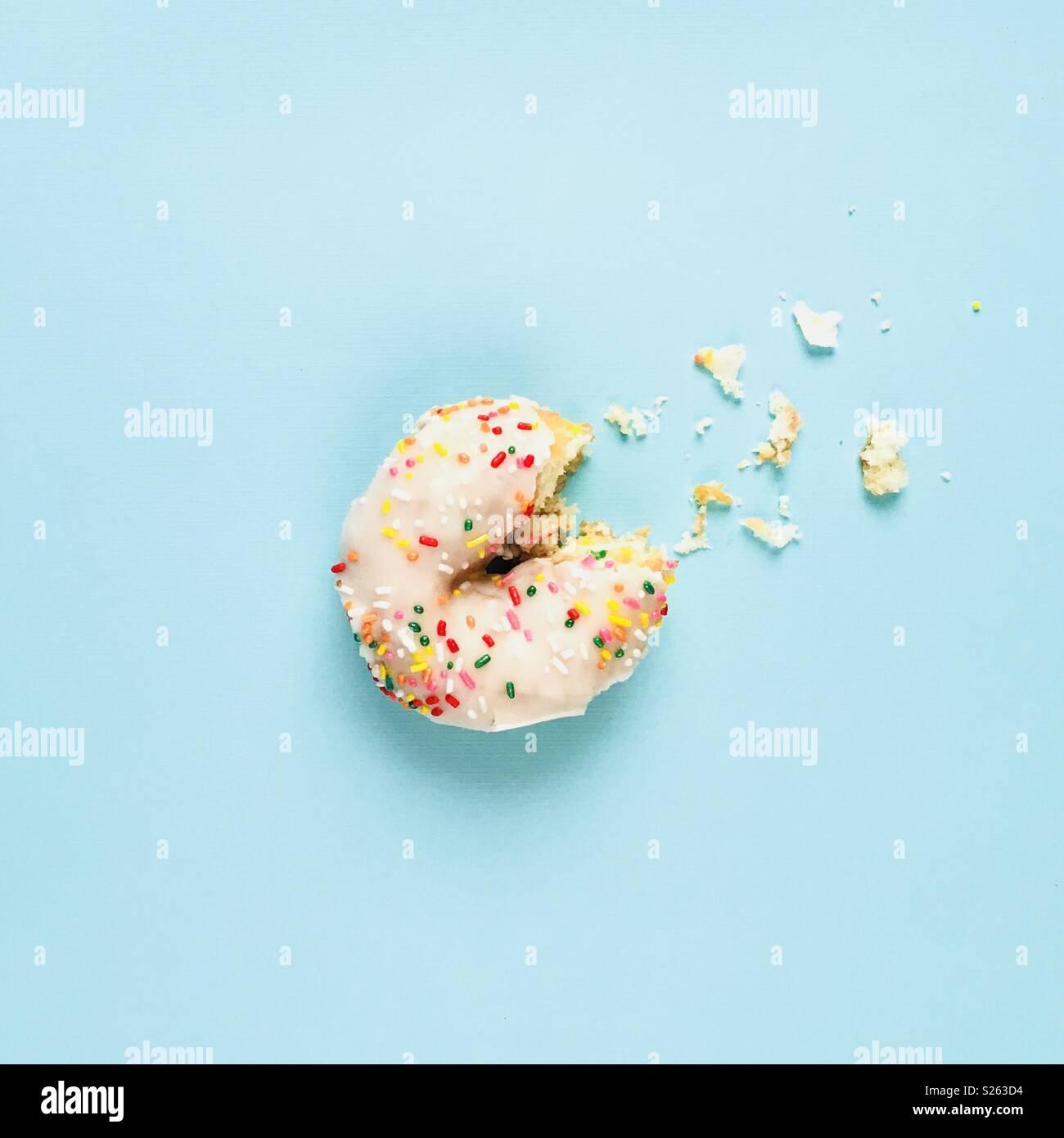 Ein weißer Sprühregen Donut mit einem Bissen aus auf einem blauen Hintergrund. Stockbild
