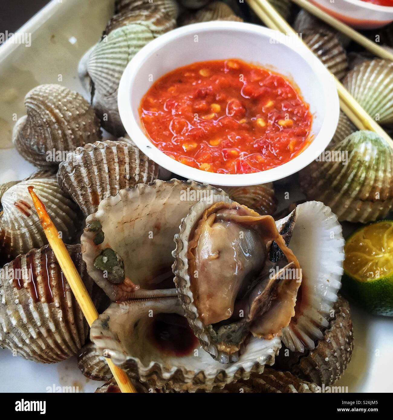 Muscheln und Chili Sauce bei East Coast Lagoon Food Village, eine Hawker Food Markt in Singapur Stockbild