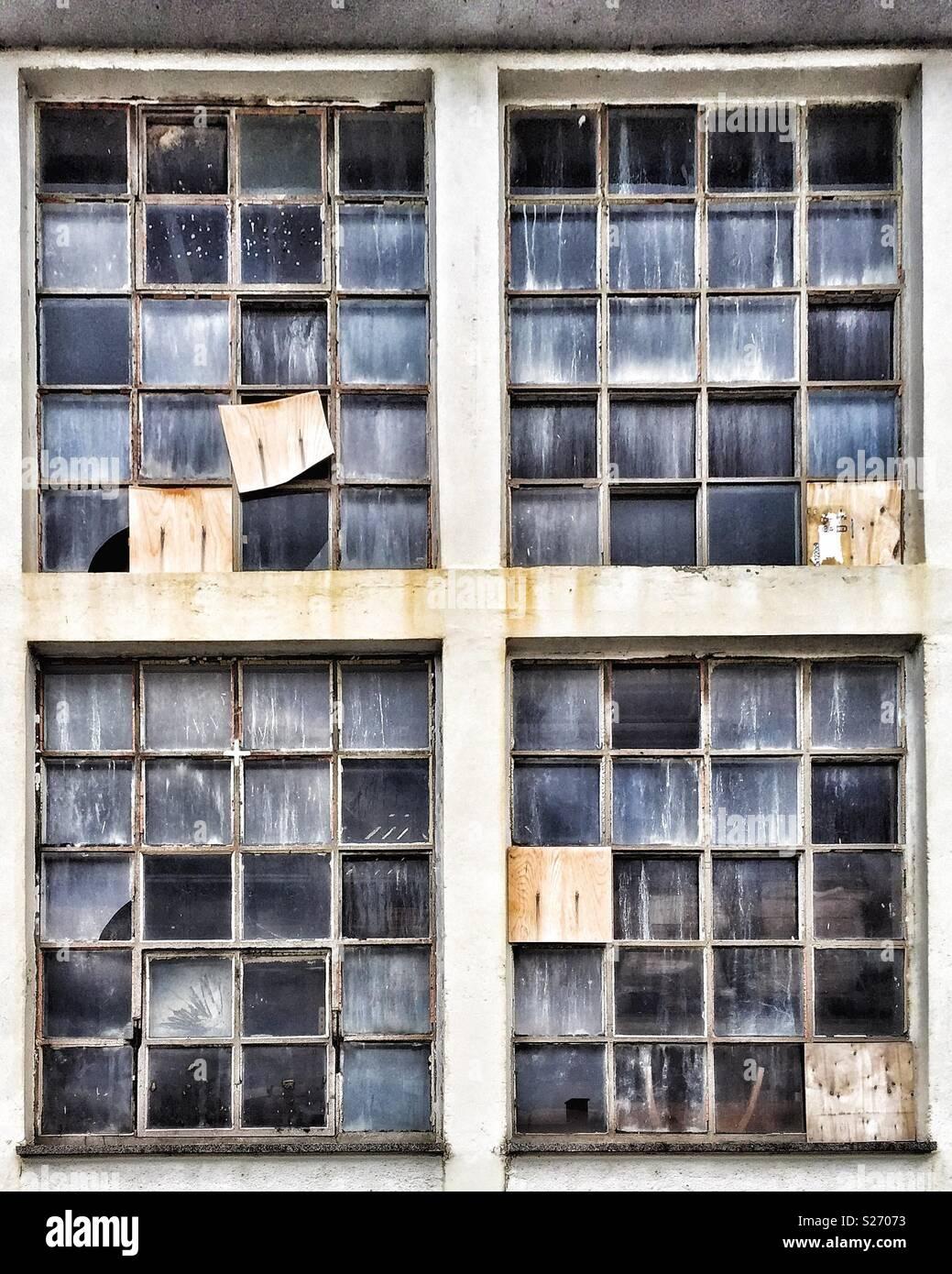 Zerbrochene Fenster an einem verlassenen Gebäude Stockbild