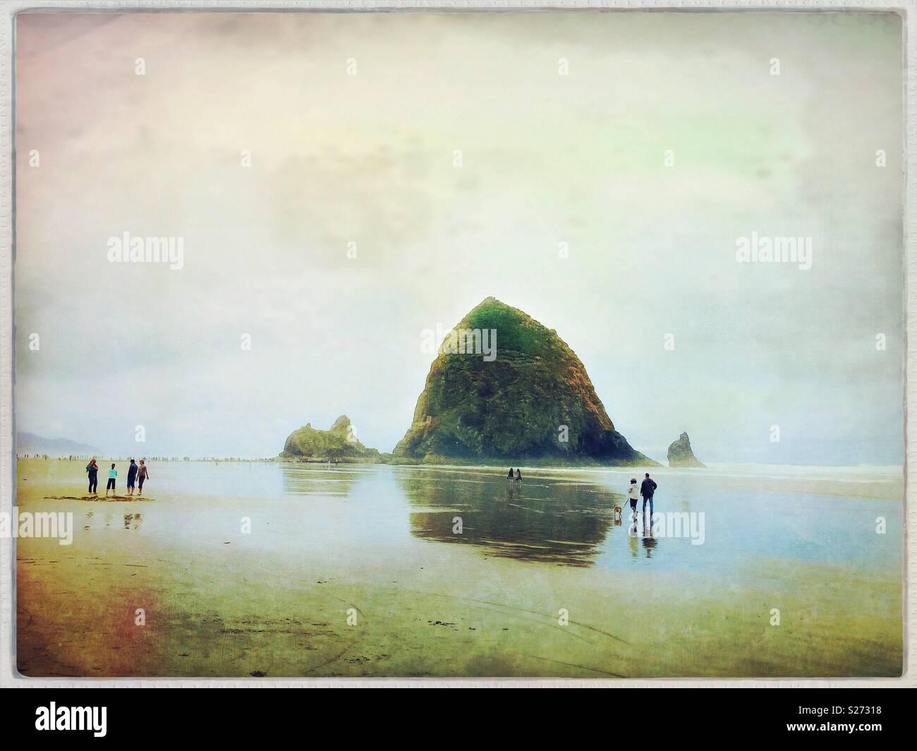 Haystack Rock mit Wanderers am Strand entlang, Cannon Beach, Oregon, USA. Stockbild
