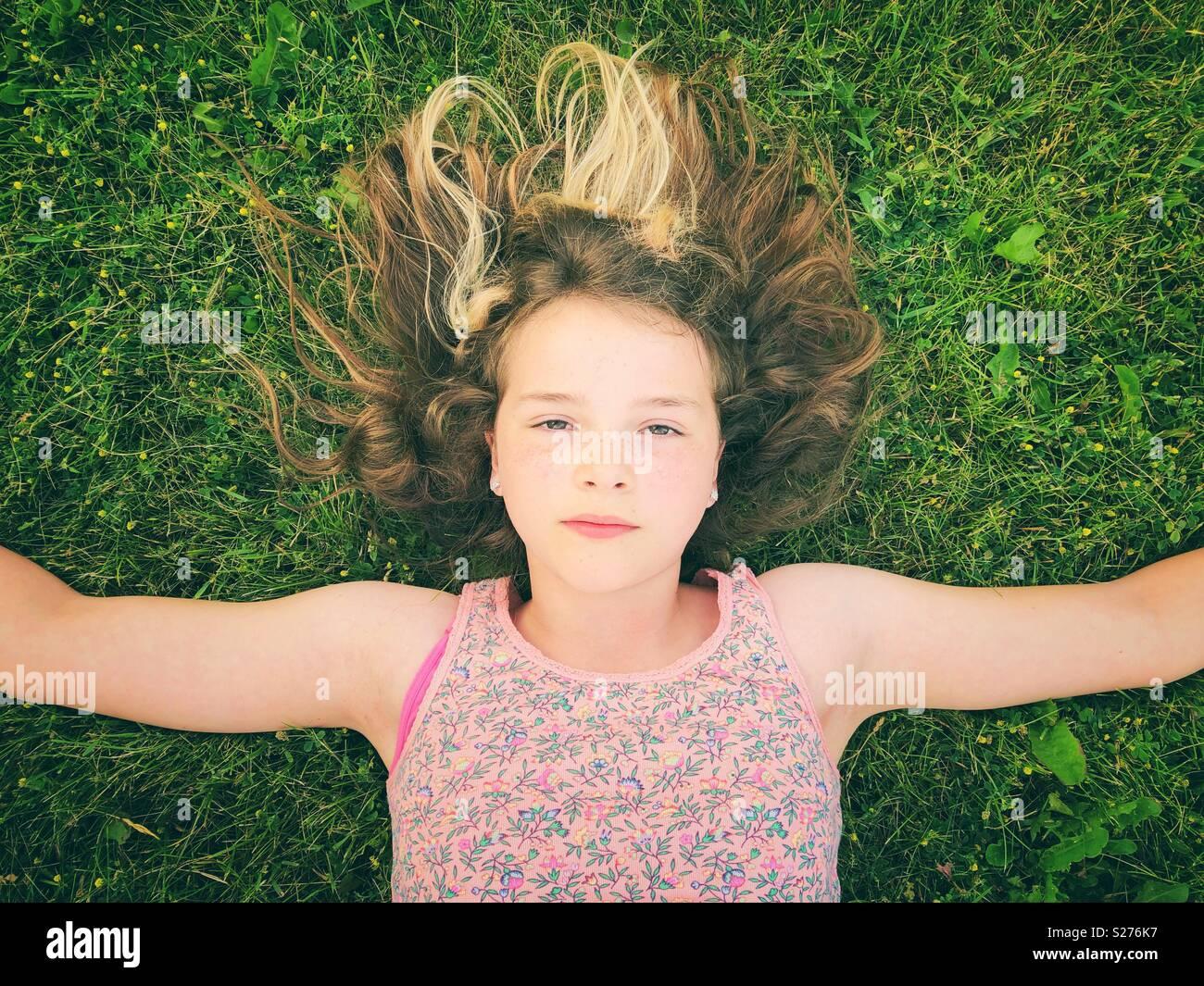 11-jährige Mädchen mit in das Gras mit Armen und ernsten Ausdruck auf ihrem Gesicht Stockbild
