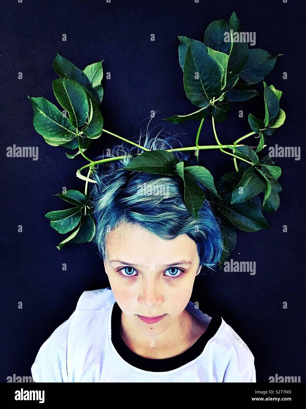 Ein Kind mit Blättern auf dem Kopf platziert. Stockbild
