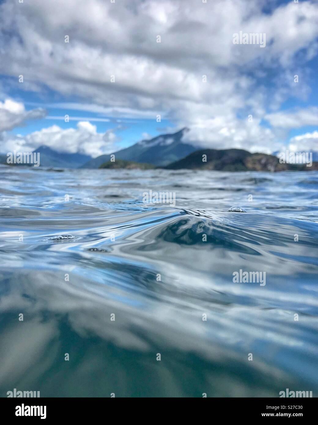 Ein Blick auf die Desolation Sound aus Wasser mit einem Gefühl von Bewegung und einem Blick auf die Berge und Himmel im Hintergrund. Stockbild