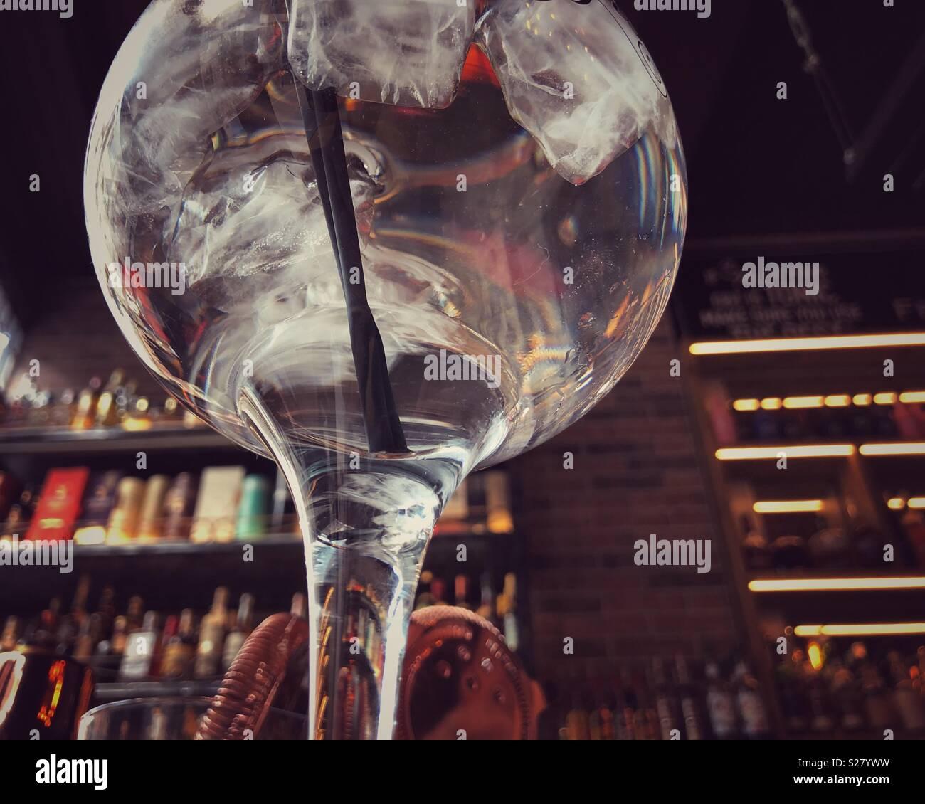 Ansicht von unten, von einem Gin Glas auf einen Stehtisch. Stockbild