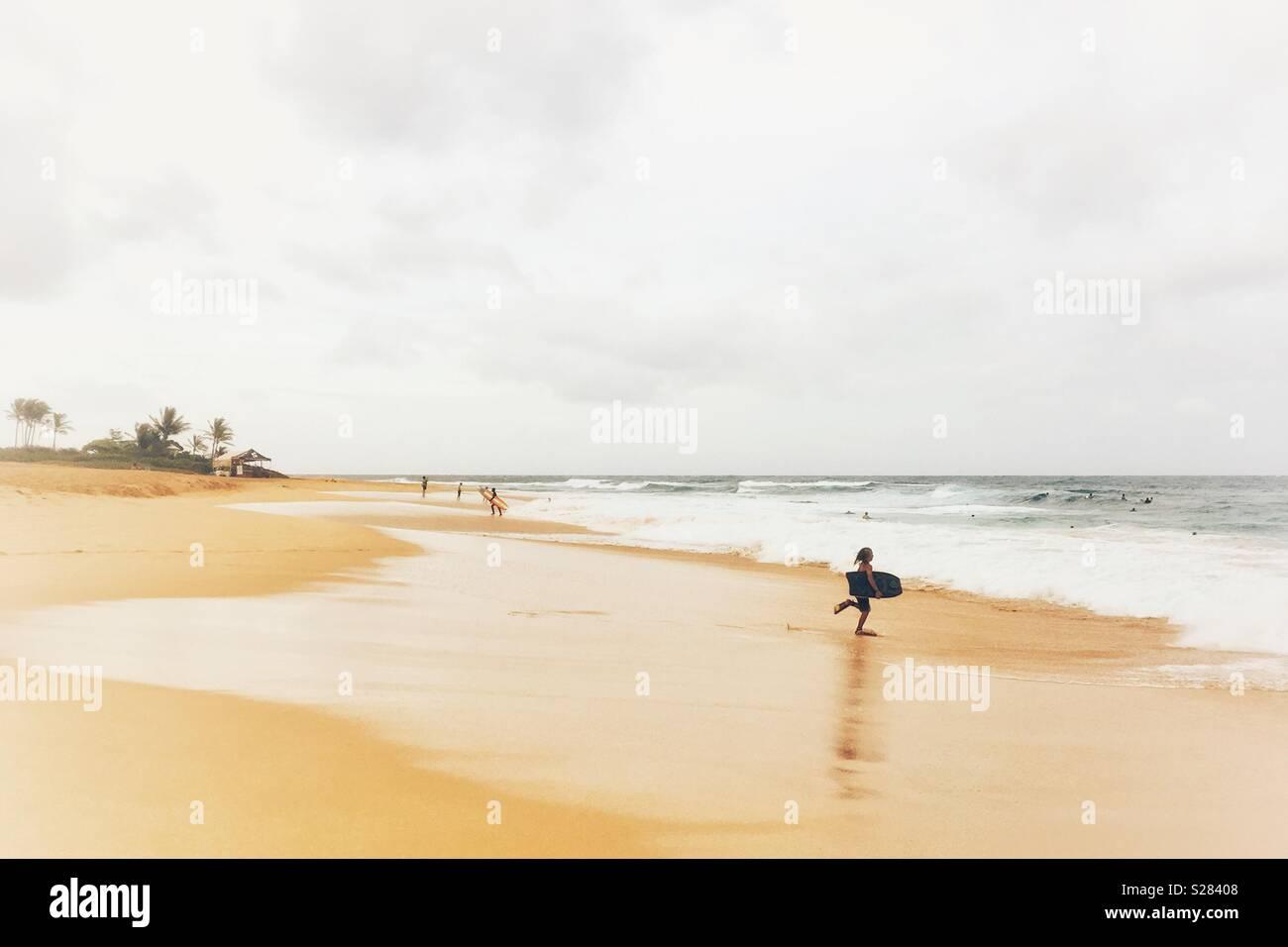Ein boogie boarder Mann mit kurzen Flossen läuft am Strand ins Meer. Platz für Kopieren. Stockbild