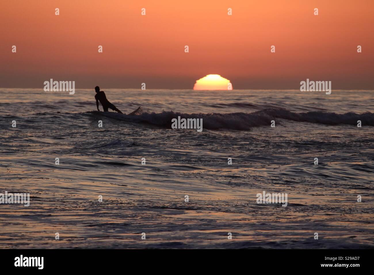 Surfer nimmt eine letzte Welle des Tages Stockfoto