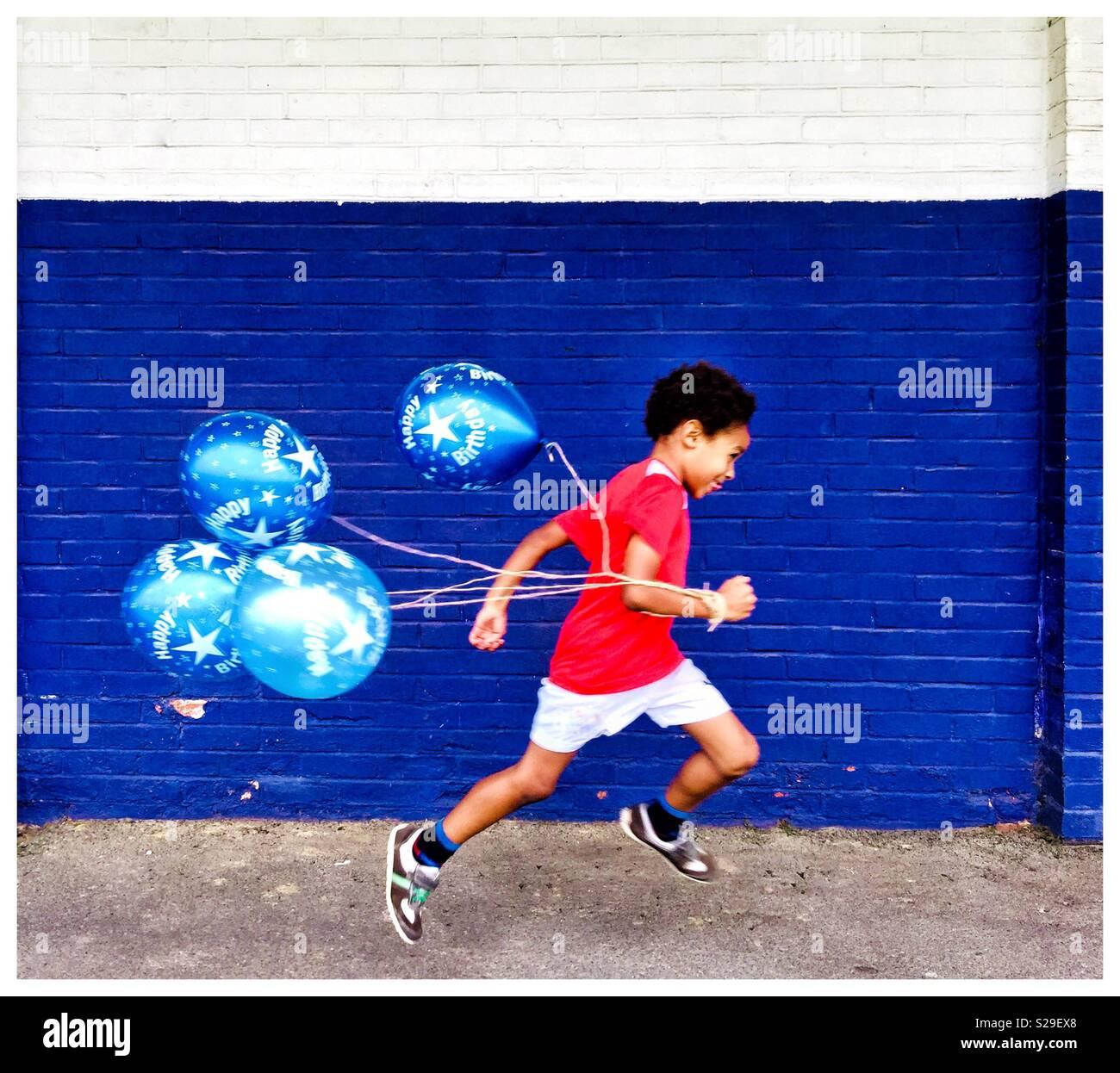 Ein kleiner Junge läuft mit Luftballons. Stockbild