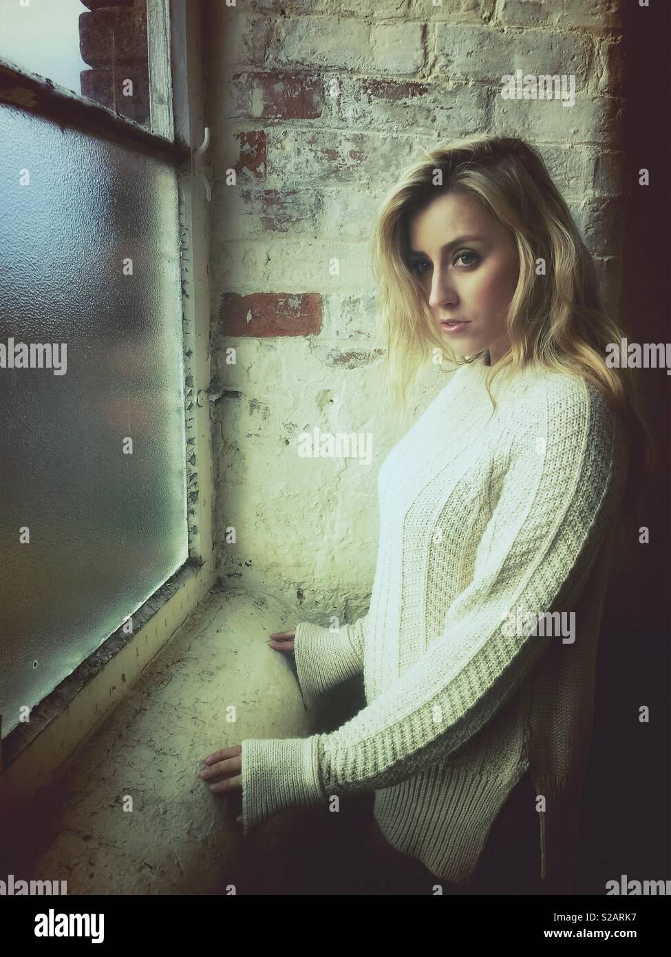 Schöne nachdenkliche blonde Frau Blick aus Fenster Stockbild