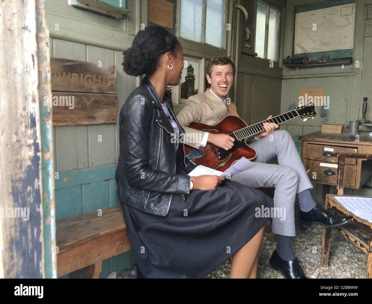 Ein paar der multirassischen Musiker genießen Gig in einem Schuppen Stockbild