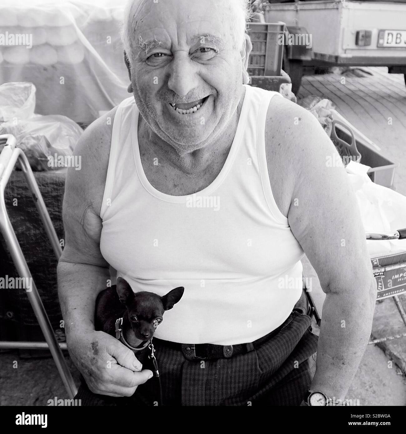 Porträt eines alten Mannes in einem weißen Weste lachend mit seinem Chihuahua auf seinem Schoß in Malta Stockfoto