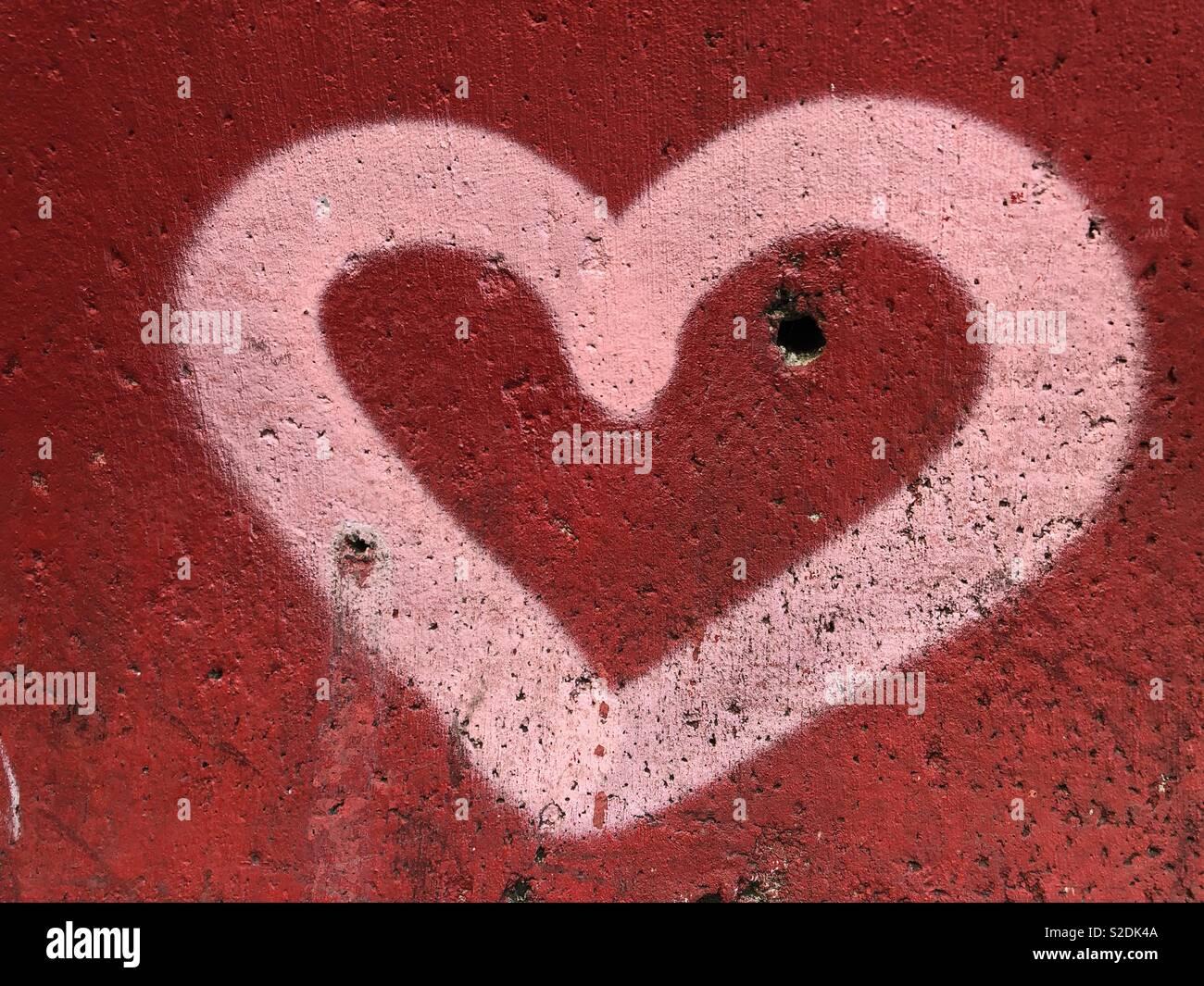 Rosa Herzen an der Wand Stockbild