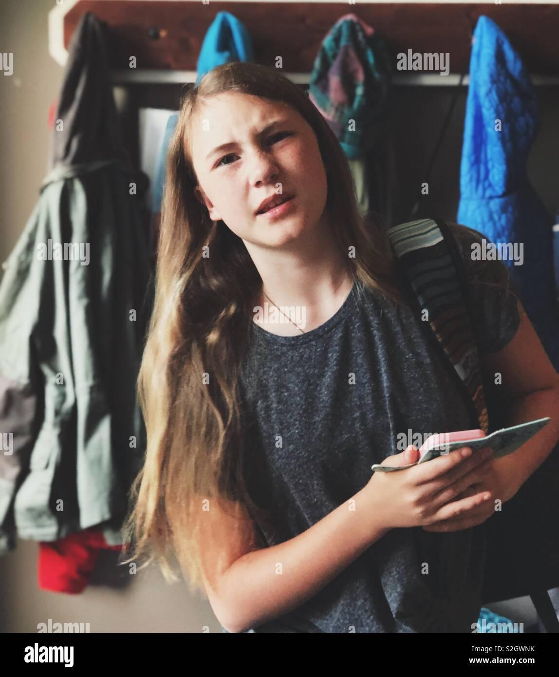 Candid Portrait von grumpy jugendlich Mädchen, dass Smartphone Stockbild