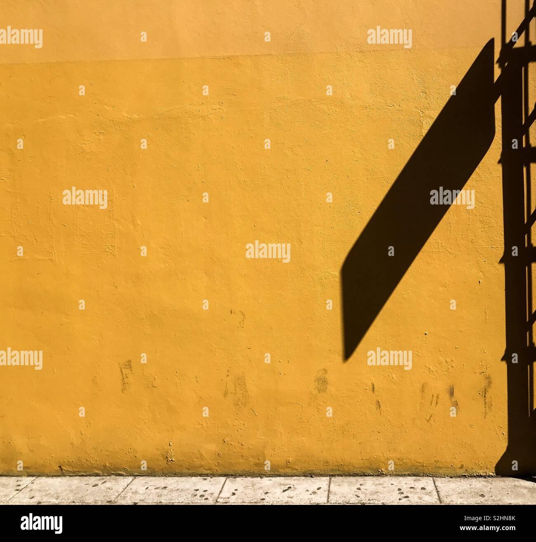 Schatten des Gesetzes. Schatten der Straßenschild auf der hellen gelben wand. Oaxaca de Juárez, Oaxaca, Mexiko. 16 Februar, 2019 Stockbild