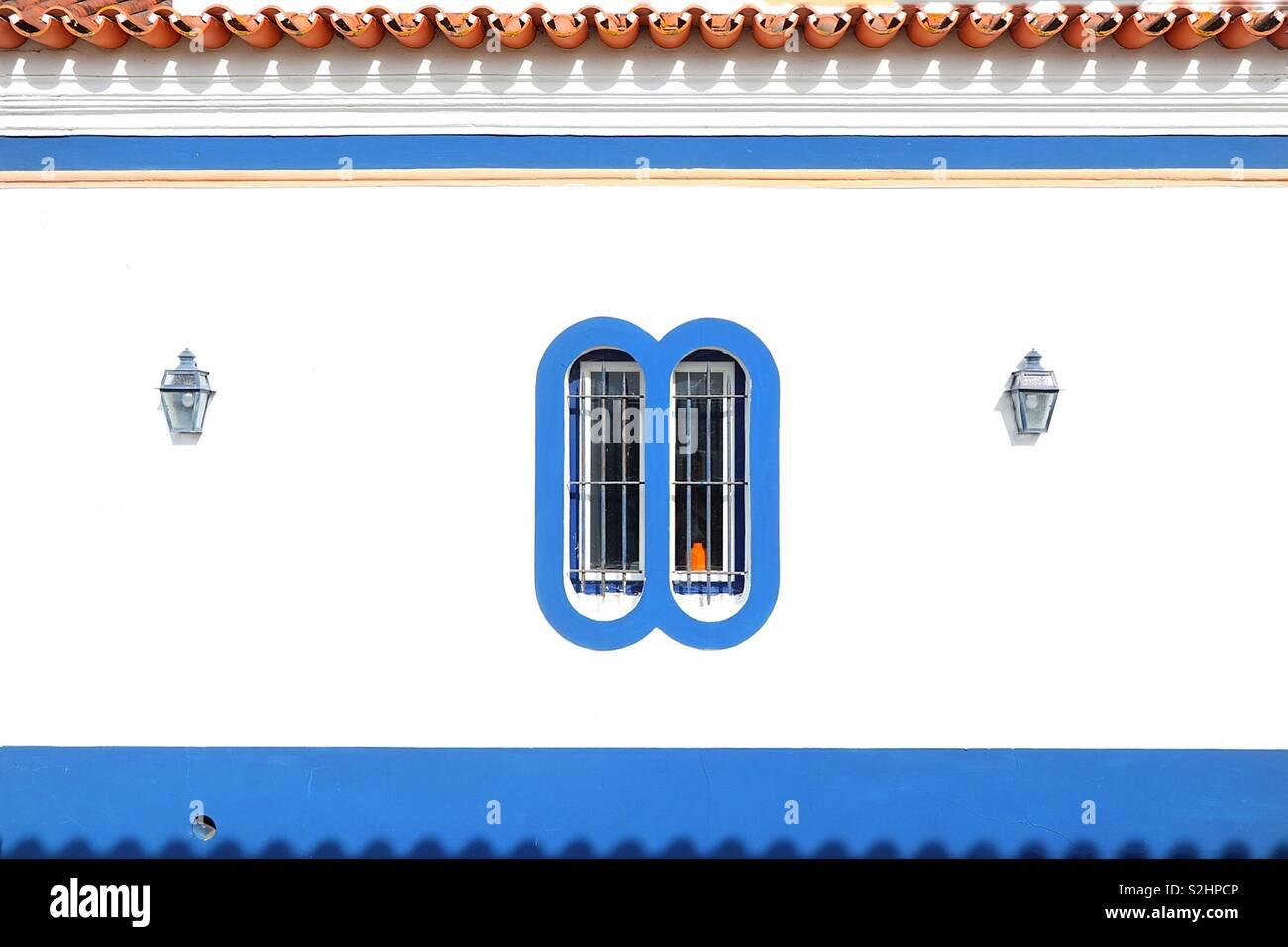 Blaues Fenster in eine weiße Wand mit zwei Leuchten Stockbild