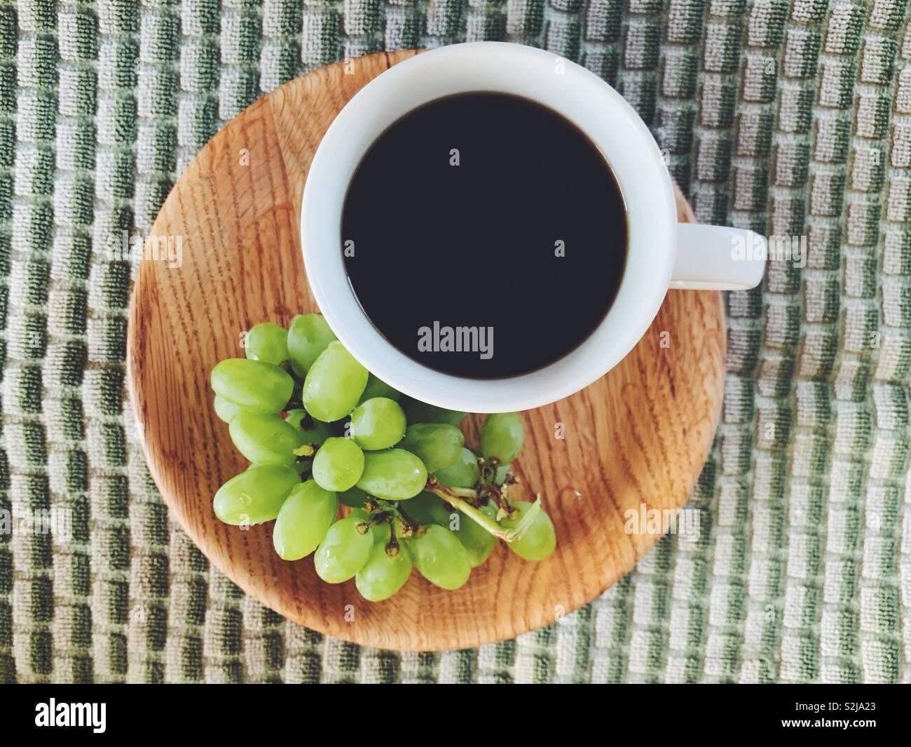 Kaffee und Trauben auf einer Platte Stockbild