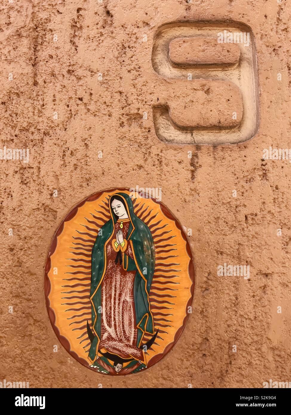 Eine Nummer neun und ein Bild Unserer Lieben Frau von Guadalupe in einem orange Wand in Coyoacan, Mexiko Stockbild