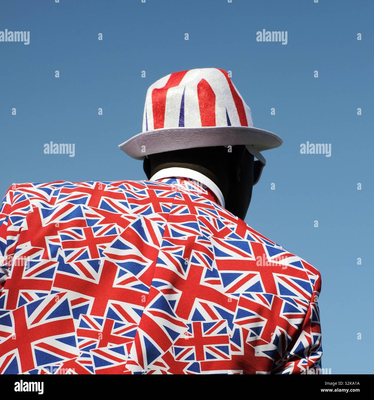 Ein sehr britischer Mann - ein Mann, der einen Flaggenanzug und Hut von Union Jack UK trägt - nationalistisch-patriotisch Stockfoto