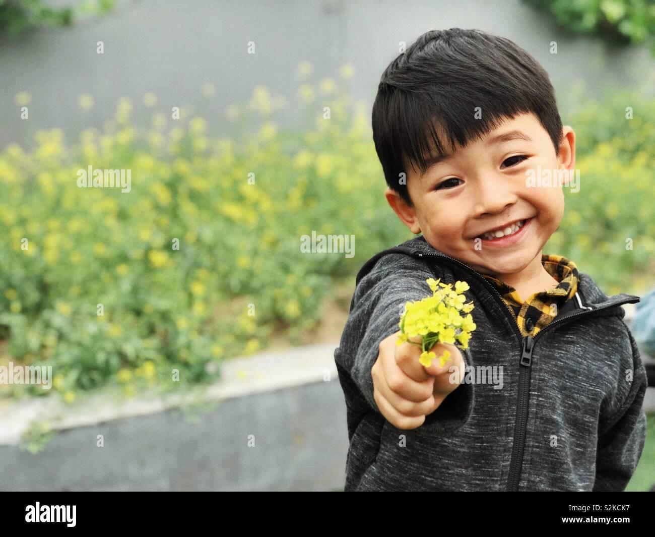 Little Boy und Blumen Stockfoto