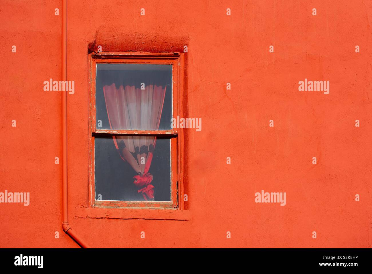 Rote Wand mit Fenster Stockfoto