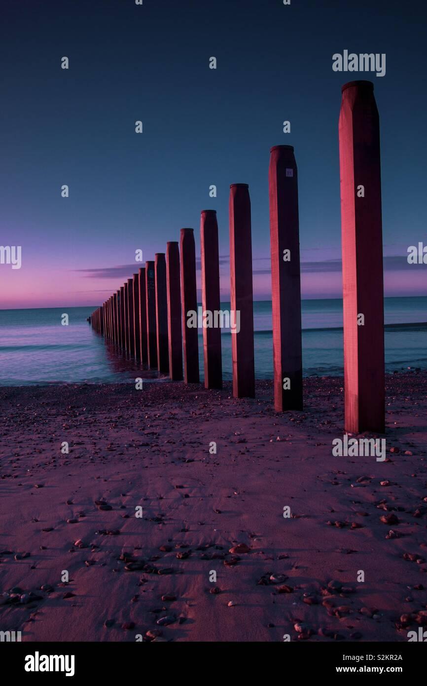 Buhnen am Meer bei Sonnenaufgang, geometrischen Linien, Schönheit in der Natur Stockfoto