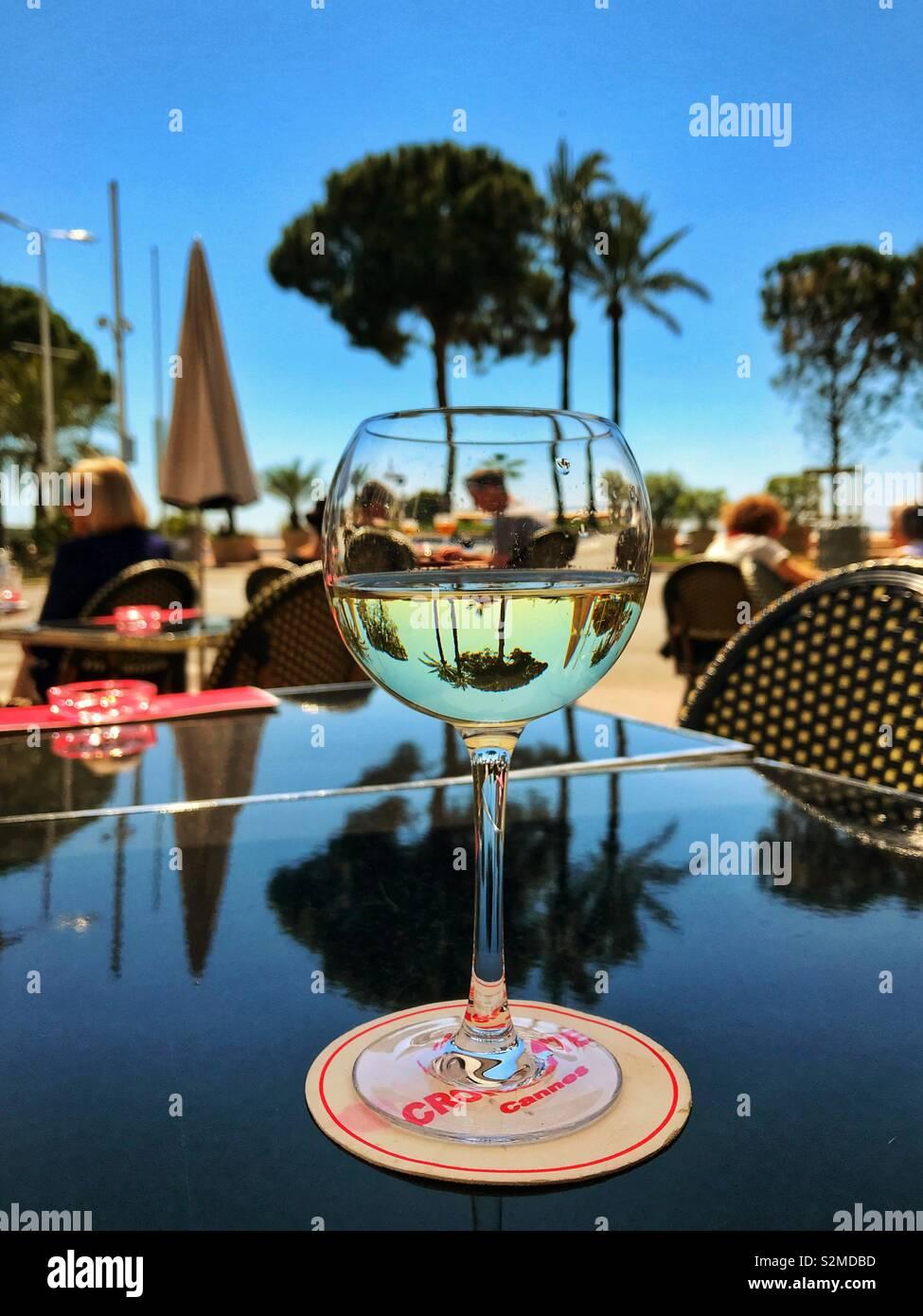Glas Weißwein auf einem Tisch in einem Restaurant am Meer in Cannes, Frankreich Stockfoto