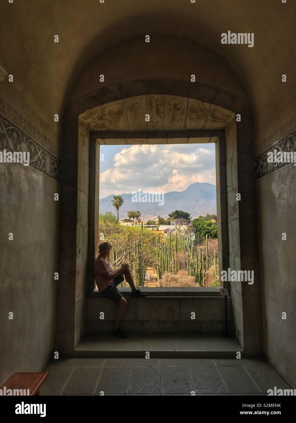 Mann ruht in Fenster mit Blick auf die Gärten des Museums der Kulturen von Oaxaca, Santo Domingo, Oaxaca City, Oaxaca, Mexiko Stockbild