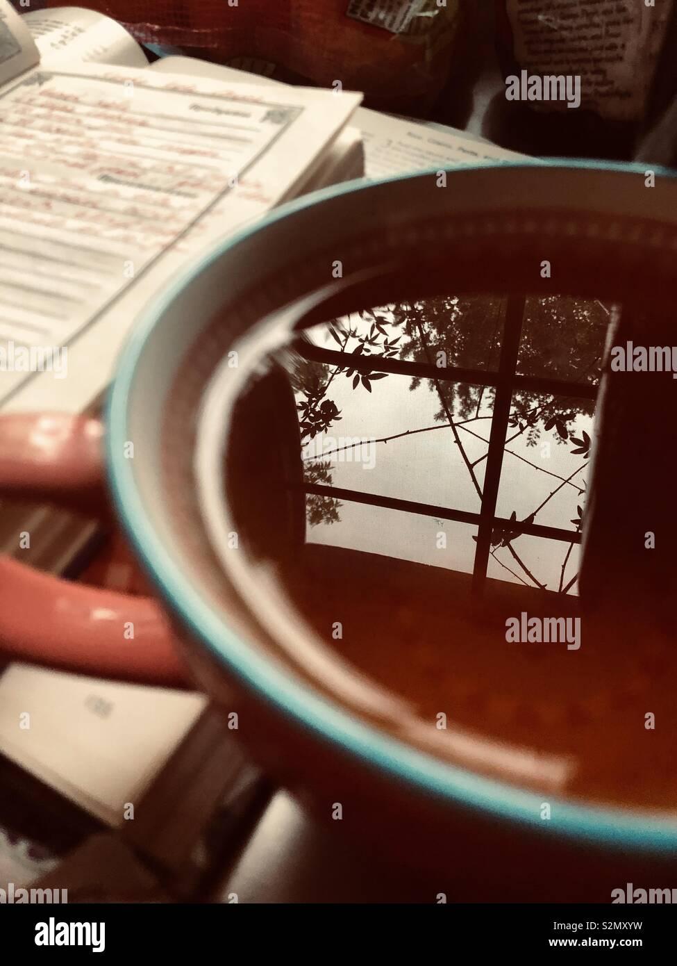 Nahaufnahme von einer Tasse schwarzen Tee mit einem Fenster Reflexion, und eine handgeschriebene Notizen in ein Notebook im Hintergrund Stockfoto