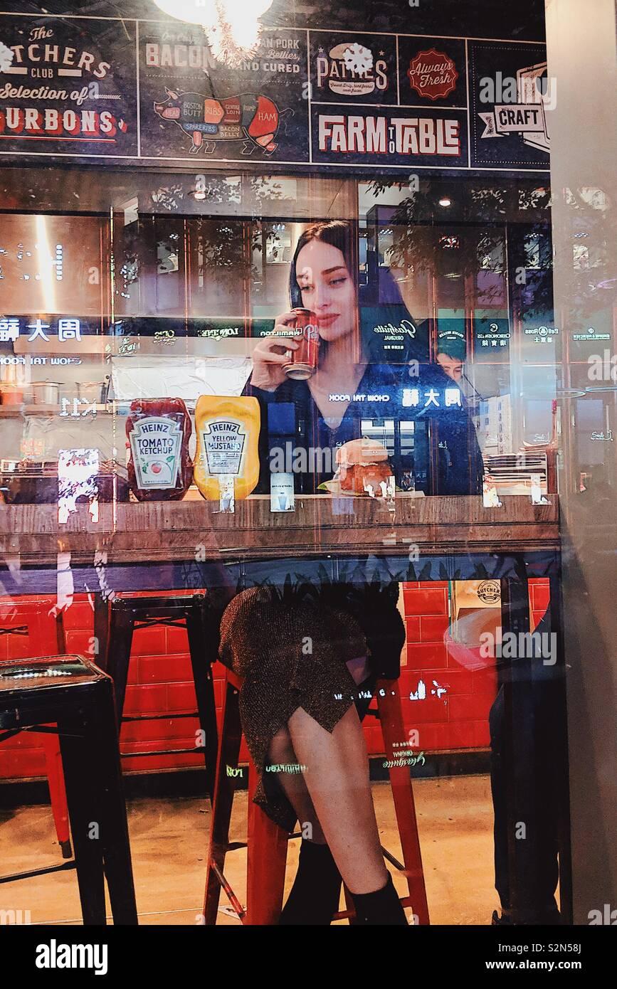 Mädchen Fast Food essen und trinken Coca-Cola. Stockfoto