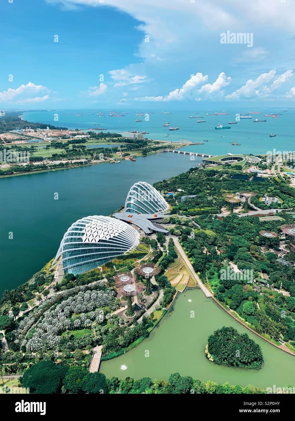 Blick vom 57. Stock des Marina Bay Sands übersicht Gärten durch die Bucht, Super Bäume, Blumen Dome, Nebelwald und Schiffe im Hafen Stockfoto