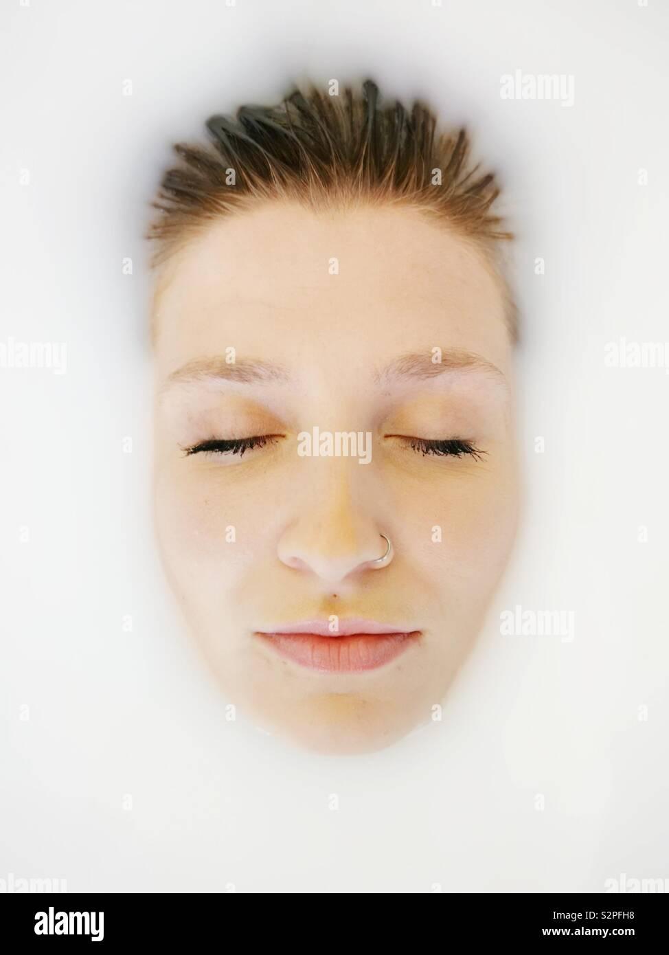 In der Nähe von Mädchen Gesicht in einer Badewanne von Milch Stockfoto