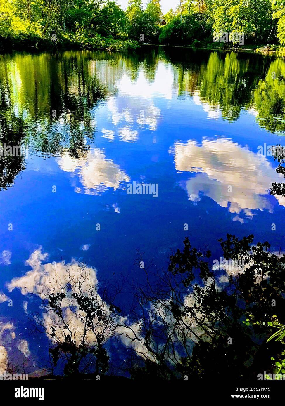 Spiegelbild der Himmel und Wolken im Wasser Stockbild