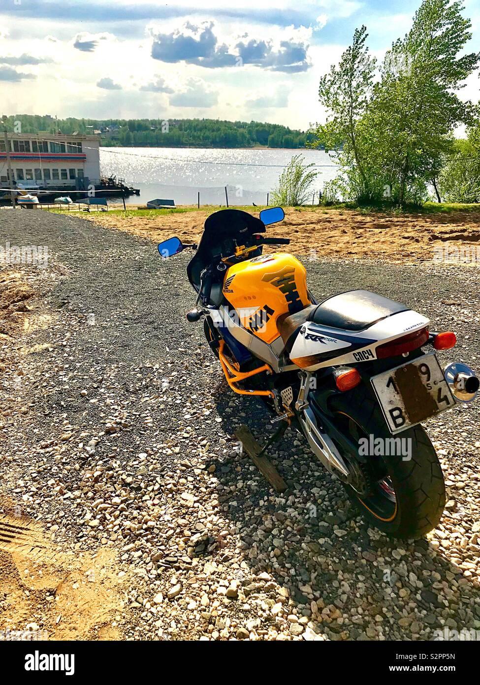 Motorrad am Ufer des Flusses Stockbild