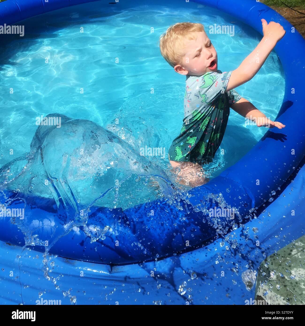 Zwei Jahre alten Jungen Spritzen in das Planschbecken zur Verfügung. Stockfoto