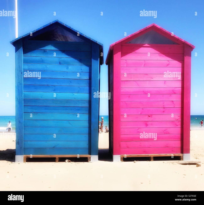 Zwei bunten Holzhütten an einem Sandstrand, ein Licht blau, die anderen rosa, eingesetzt als Umkleidekabinen. Stockfoto