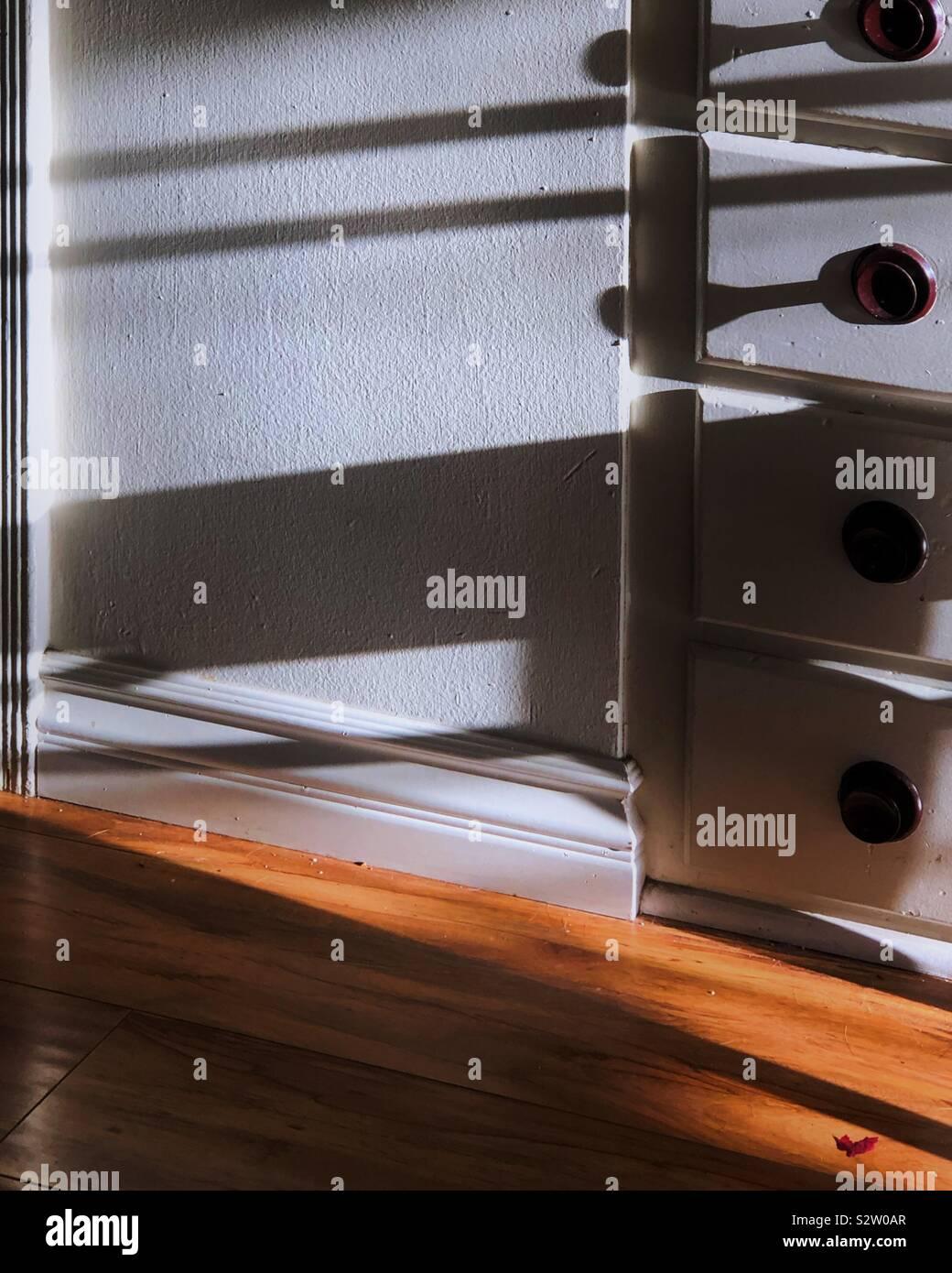 Am frühen Abend Schatten, die sich über einen eingebauten Schreibtisch und Schrank. Die Hartholzböden kick up viel Umgebungslicht. Stockfoto
